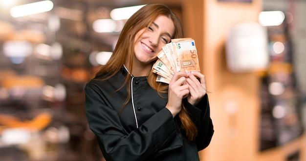 돈을 들고 젊은 빨강 머리 요리사 여자