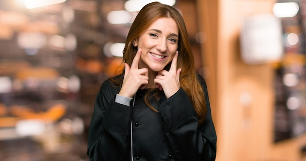 Young redhead chef woman smiling with a happy and pleasant expression in the bakery