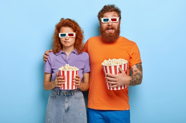 Young redhead couple spend free time in 3d cinema, eat popcorn, wear special glasses for visual effects, bearded excited guy embraces lovely girlfriend who has bored expression, doesnt like film