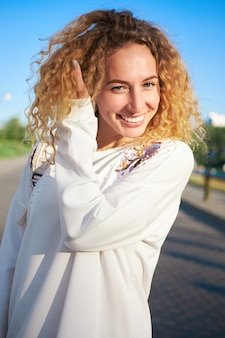 Young redhead curly white woman in white dress laughing.