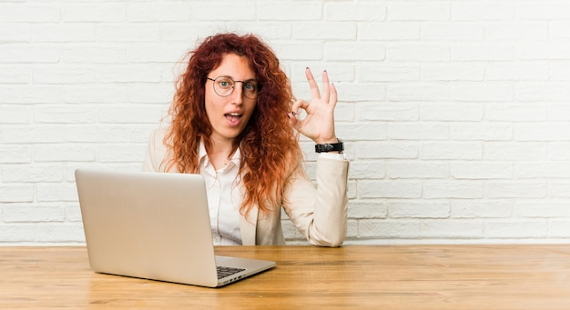 Young redhead curly woman working with her laptop cheerful and confident showing ok gesture.