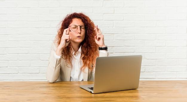 Молодая рыжая кудрявая женщина работает со своим ноутбуком, скрещивая пальцы для удачи