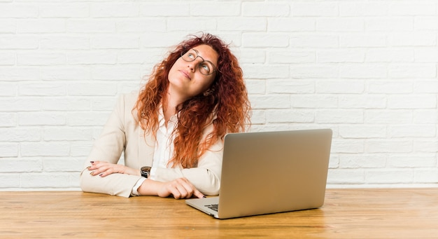 Young redhead curly woman working with her laptop dreaming of achieving goals and purposes