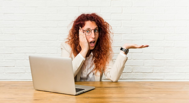 Young redhead curly woman working with her laptop holds copyspace on a palm, keep hand over cheek. amazed and delighted.