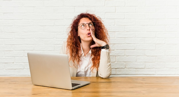 Young redhead curly woman working with her laptop is saying a secret hot braking news and looking aside