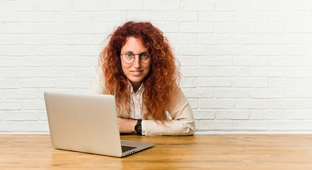 Young redhead curly woman working with her laptop laughing and having fun.