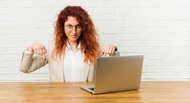 Young redhead curly woman working with her laptop points down with fingers, positive feeling.