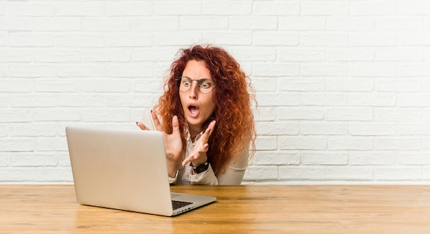 Young redhead curly woman working with her laptop shouts loud, keeps eyes opened and hands tense.