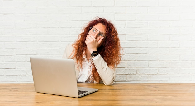Young redhead curly woman working with her laptop thoughtful looking to a copy space covering mouth with hand.