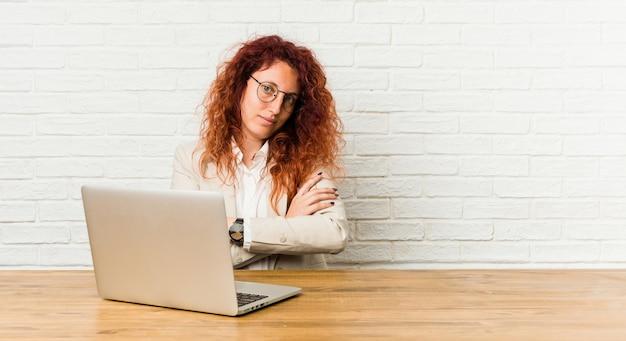Молодая рыжая кудрявая женщина работает со своим ноутбуком, который чувствует себя уверенно, скрестив руки с решимостью