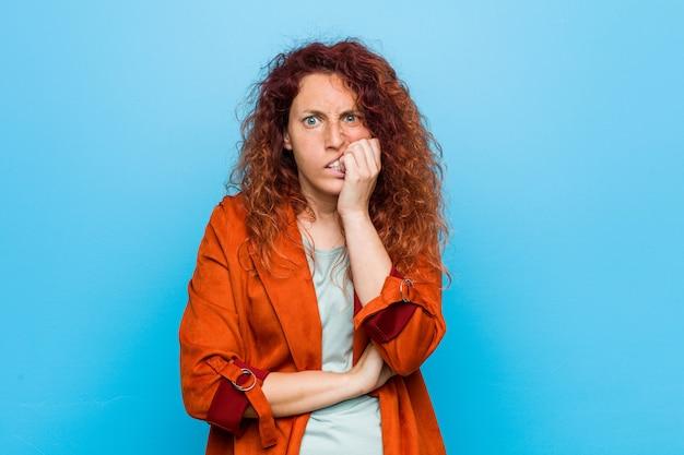 若い赤毛のエレガントな女性の爪をかむ、緊張し、非常に心配。