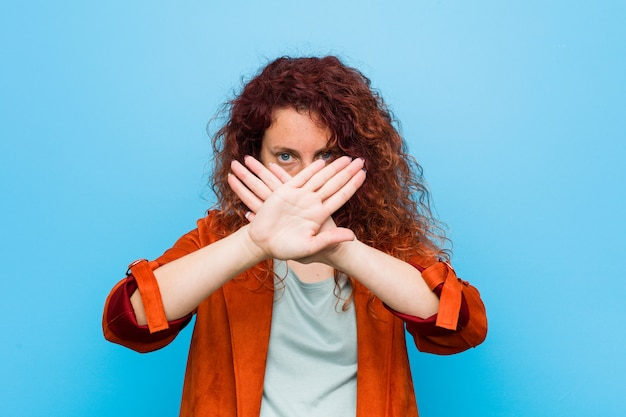 Young redhead elegant woman doing a denial gesture