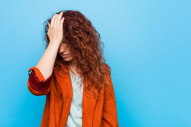 Young redhead elegant woman forgetting something, slapping forehead with palm and closing eyes.