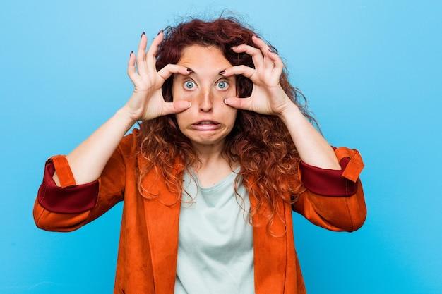 Молодая рыжая элегантная женщина держит глаза открытыми, чтобы найти возможность успеха.