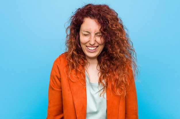 Young redhead elegant woman laughs and closes eyes, feels relaxed and happy.