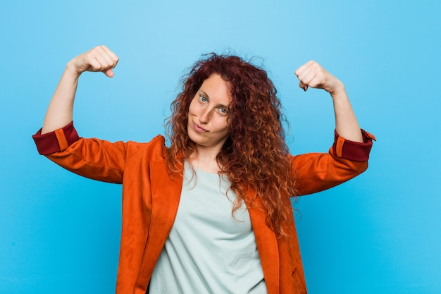 Young redhead elegant woman showing strength gesture with arms, symbol of feminine power