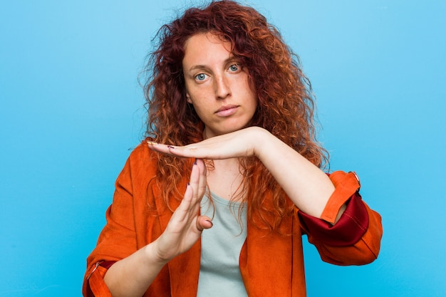 Young redhead elegant woman showing a timeout gesture.