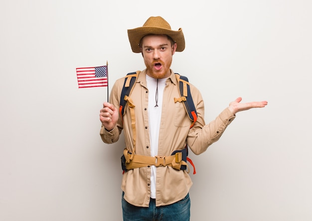 Young redhead explorer man holding something on palm hand. holding an united states flag.