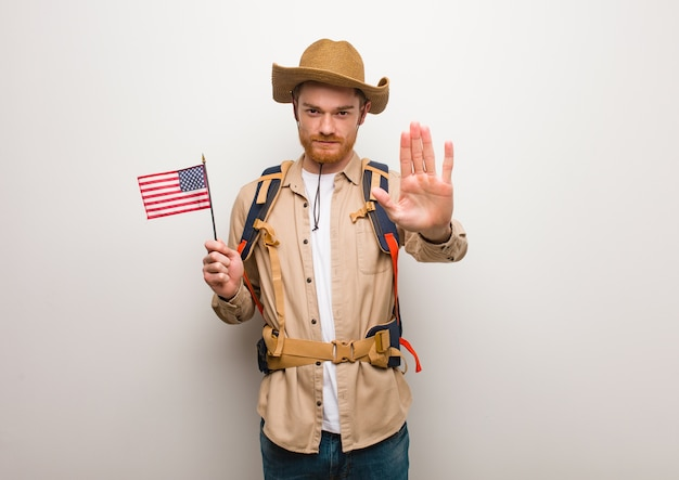 Young redhead explorer man putting hand in front. holding an united states flag.
