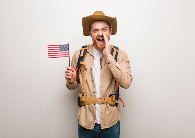 Young redhead explorer man shouting something happy to the front. holding an united states flag.