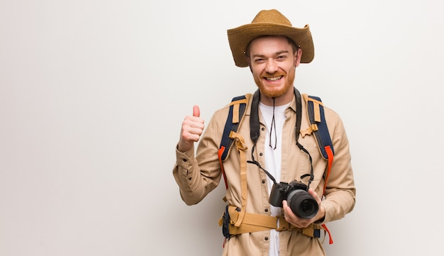 Young redhead explorer man smiling and raising thumb up. holding a camera.