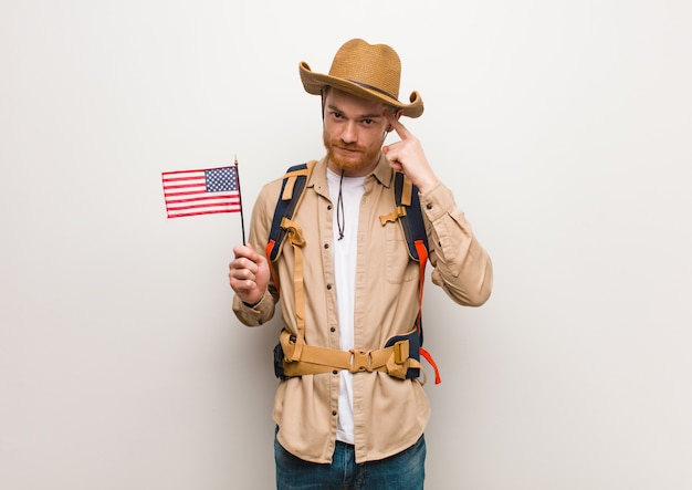 Young redhead explorer man thinking about an idea holding an united states flag