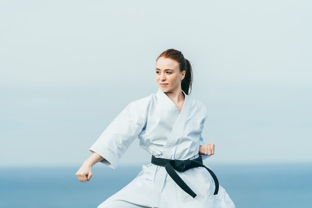 Young redhead female karate athlete training outdoor.