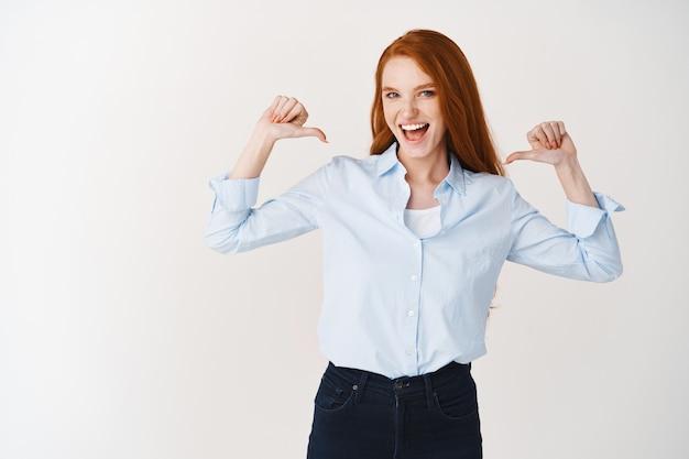 흰색 벽 위에 서서 자신을 가리키며 자신감 있게 웃고 있는 젊은 빨간 머리 여성