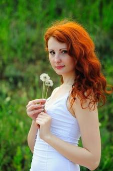 タンポポと若い赤毛の女性。
