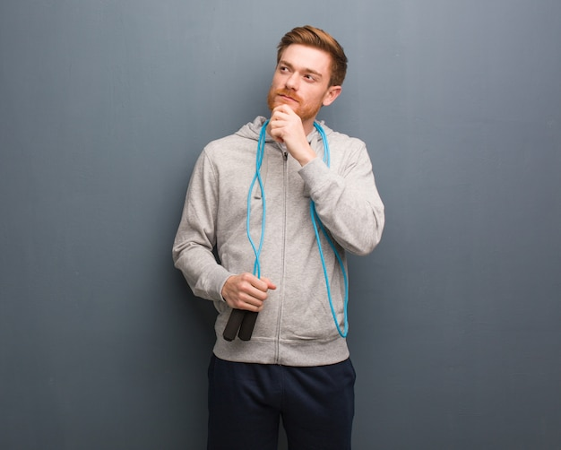 Young redhead fitness man doubting and confused. he is holding a jump rope.