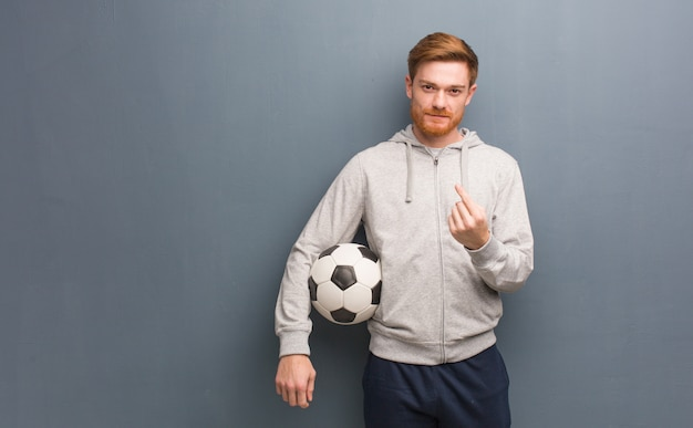 Young redhead fitness man inviting to come. he is holding a soccer ball.