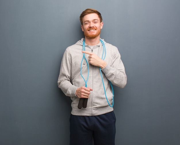 Young redhead fitness man pointing to the side with finger. he is holding a jump rope.