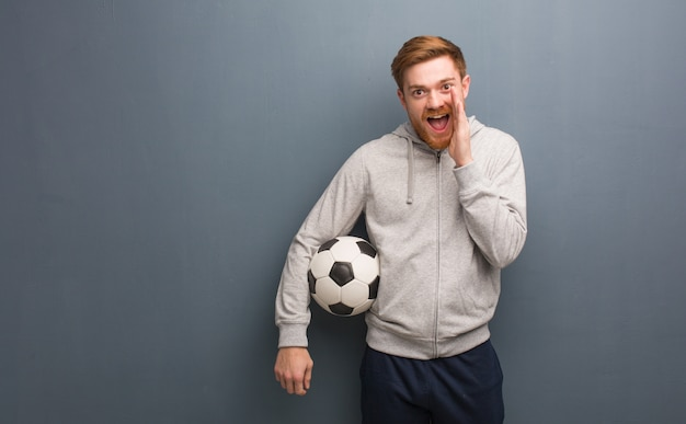 Young redhead fitness man shouting something happy to the front. he is holding a soccer ball.