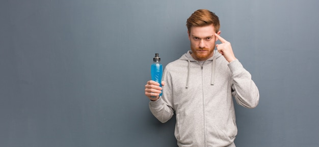 Young redhead fitness man thinking about an idea he is holding an energy drink