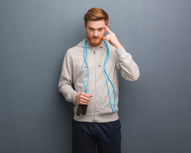 Young redhead fitness man thinking about an idea. he is holding a jump rope.
