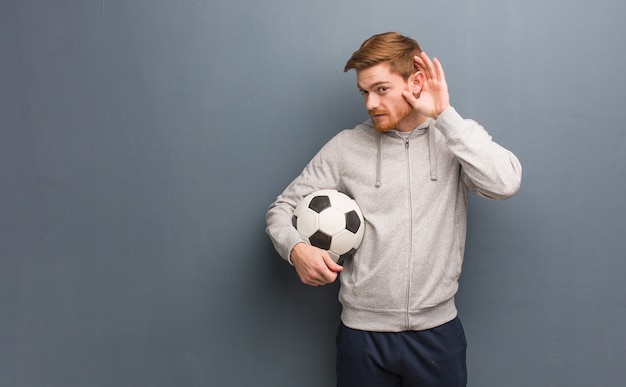 Young redhead fitness man try to listening a gossip. he is holding a soccer ball.