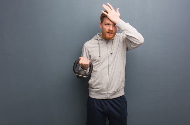 Young redhead fitness man worried and overwhelmed. holding a dumbbell.