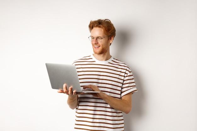 ラップトップで作業し、コンピューターのキーボードで入力し、笑顔で、白い背景の上に立っている若い赤毛のフリーランサー。