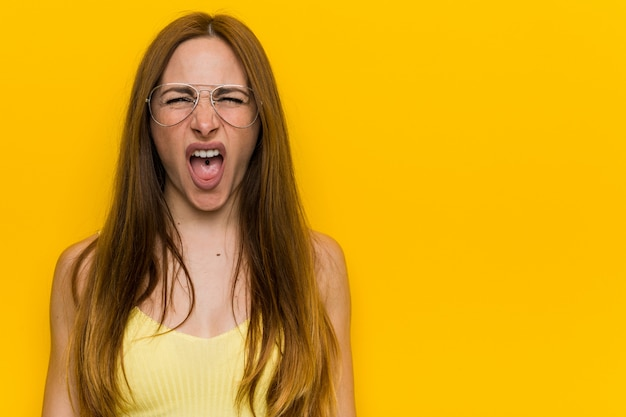 Young redhead ginger woman with freckless screaming very angry and aggressive.