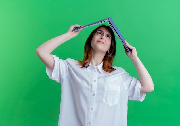 Молодая рыжая девушка прикрыла голову папкой на зеленом фоне