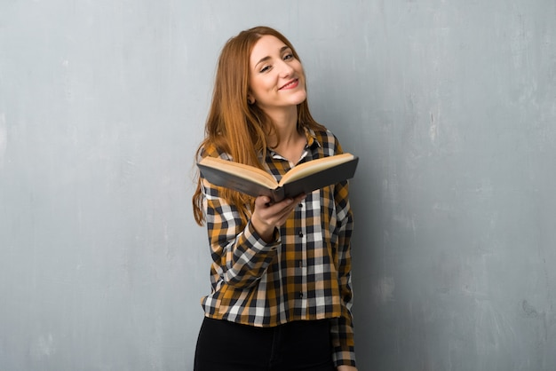 Young redhead girl over grunge wall holding a book and giving it to someone