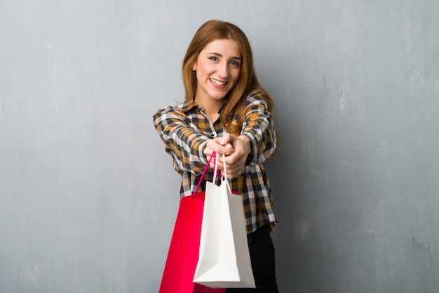 Young redhead girl over grunge wall holding a lot of shopping bags