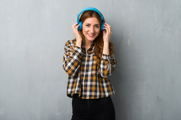 Young redhead girl over grunge wall listening to music with headphones