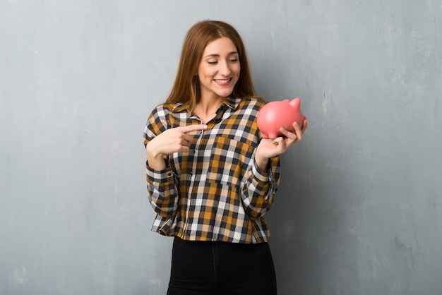 Young redhead girl over grunge wall surprised while holding a piggybank