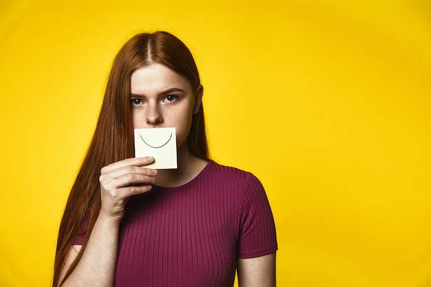 Young redhead girl has serious look and keeps a card with smile on her mouth