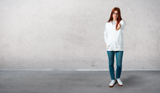 Молодая рыжая девочка в городской белой толстовке с очками, рукопожатие для закрытия