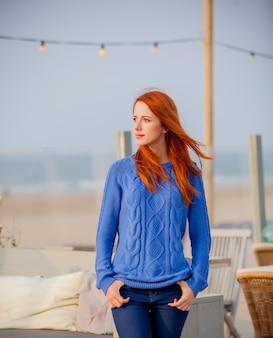 Молодая рыжая девушка в свитере bue отдыхает в кафе на пляже в гааге, нидерланды