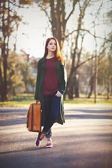 Молодая рыжая девушка в плаще с чемоданом в осеннее время на открытом воздухе