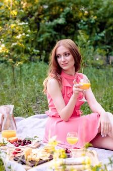 公園で夏のピクニックを持つピンクのドレスの若い赤毛の女の子。晴れた日