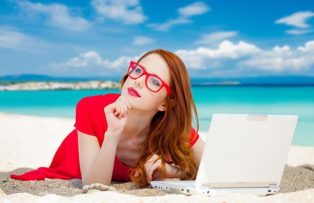 Молодая рыжая девушка в красном платье и компьютере отдыхает на летнем морском пляже